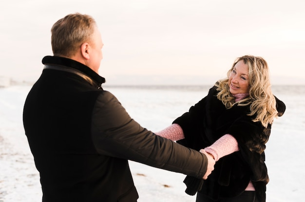 手を繋いでいるロマンチックな年配のカップル
