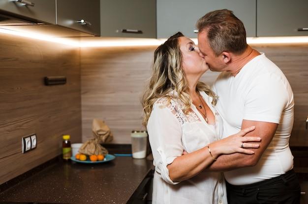 Пожилая пара целуется на кухне