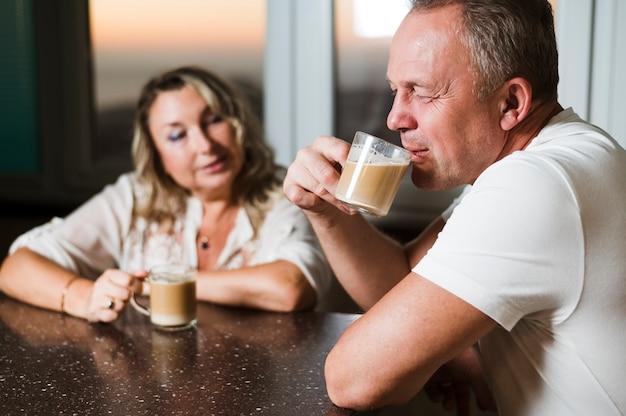Старший мужчина пьет кофе с женой