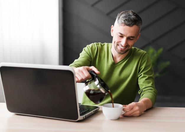 ノートパソコンとコーヒーと緑のシャツの男