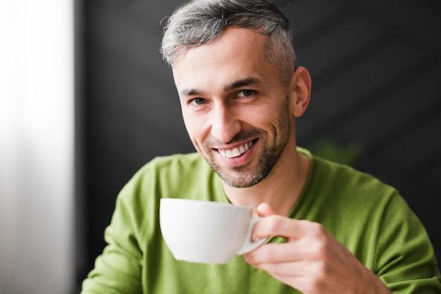 緑のシャツの男は笑顔し、一杯のコーヒーを保持