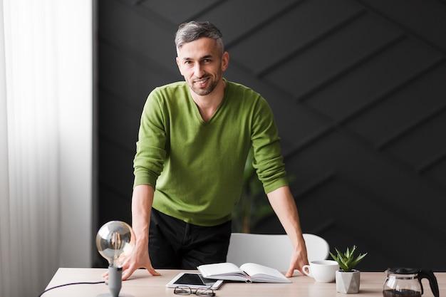 机の後ろに立っている緑のシャツの男