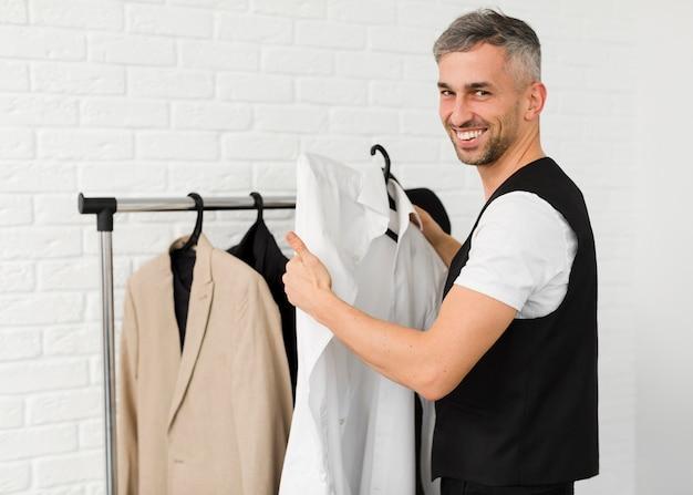 Стильный мужчина держит одежду и улыбки