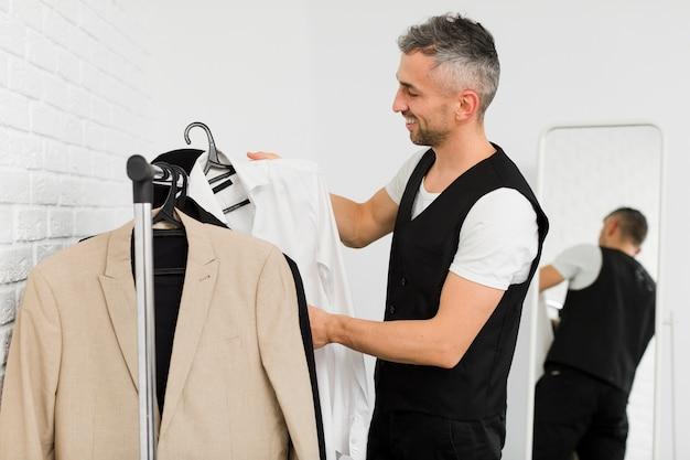 Боком мужчина расставляет одежду на вешалках