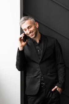 電話で話している黒のスーツを着た男