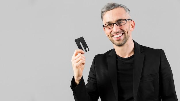 Человек в черном костюме держит кредитную карту