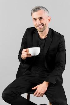Мужчина в черном костюме держит маленькую чашку чая