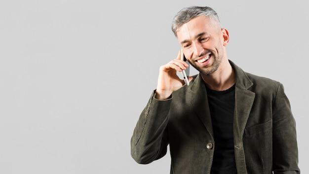 電話とコピースペースで話している灰色の髪の男性