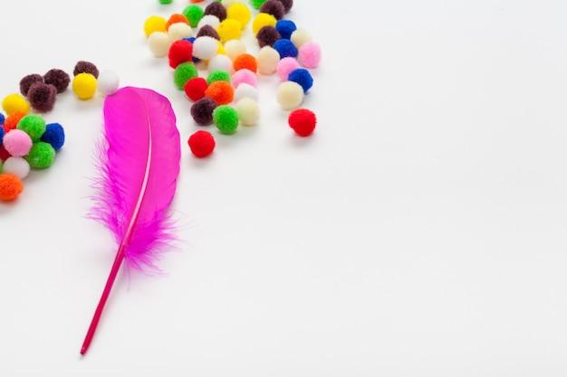 カラフルなコットンボールとピンクの羽のコピースペース