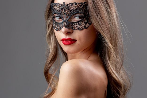 マスクを持つ豪華な若い女性
