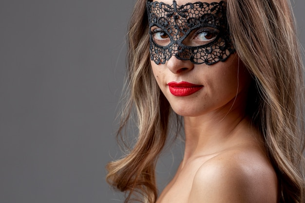 Милая молодая женщина с карнавальной маской