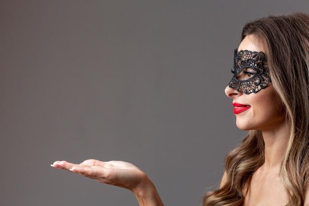 カーニバルマスクを持つかなり若い女性