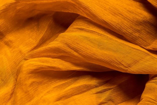 滑らかでエレガントなオレンジ色の生地素材の質感