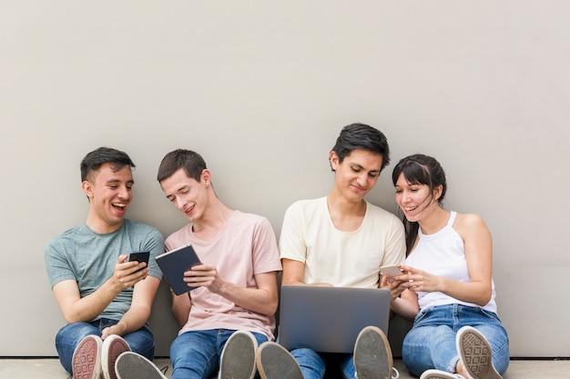 Молодые люди с телефонами и ноутбуком