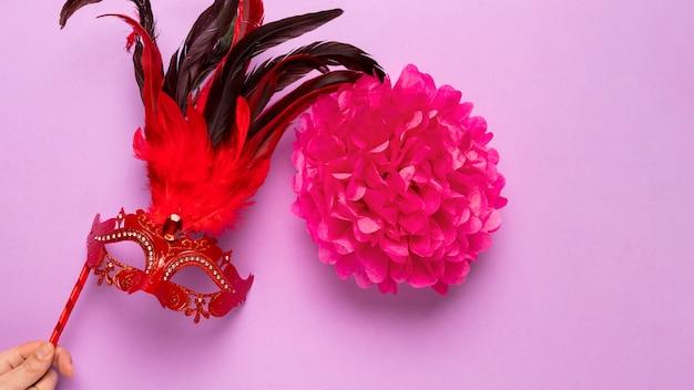 ピンクの背景の羽を持つ赤いカーニバルマスク