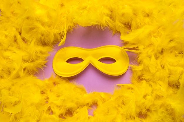 黄色の羽毛製の襟巻のクローズアップと黄色のカーニバルマスク