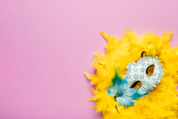 コピースペースとピンクの背景に黄色の羽毛製の襟巻と青いカーニバルマスク
