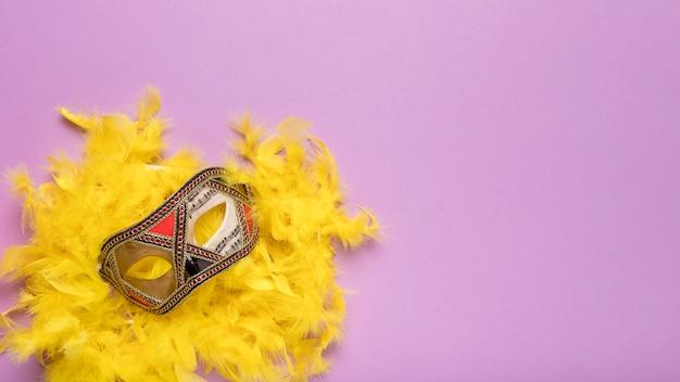 黄色の羽毛製の襟巻とコピースペースを持つ黄金のカーニバルマスク