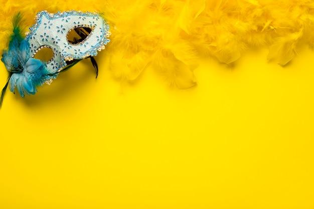黄色の羽毛製の襟巻とコピースペースを持つ青いカーニバルマスク
