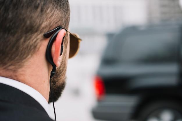 Конец-вверх охранник проверяя на автомобиле