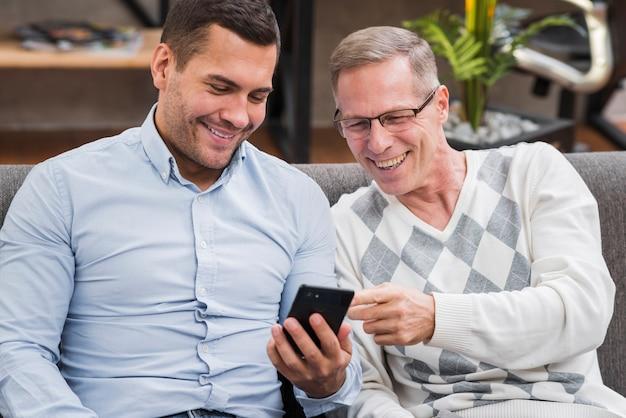 Вид спереди отца и сына, глядя на телефон