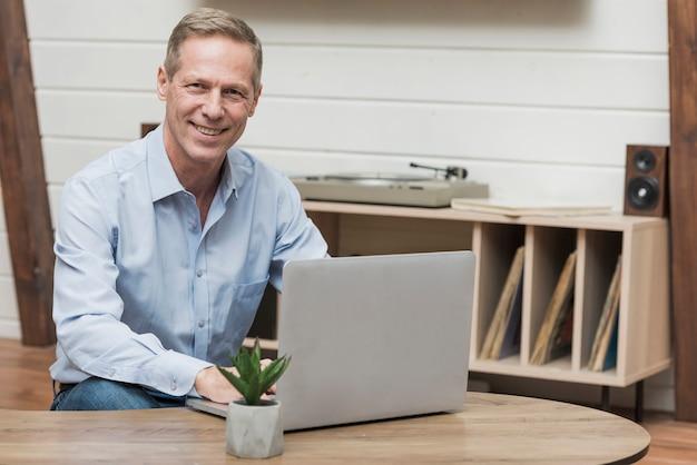 Старший мужчина, глядя через интернет на своем ноутбуке