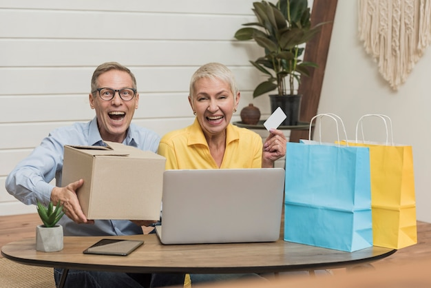 年配のカップルが彼らの買い物袋と箱を開く