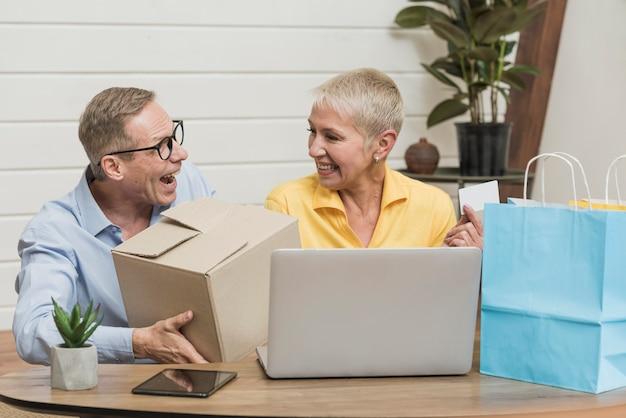 年配の男性と女性が彼らの買い物袋と箱を開く