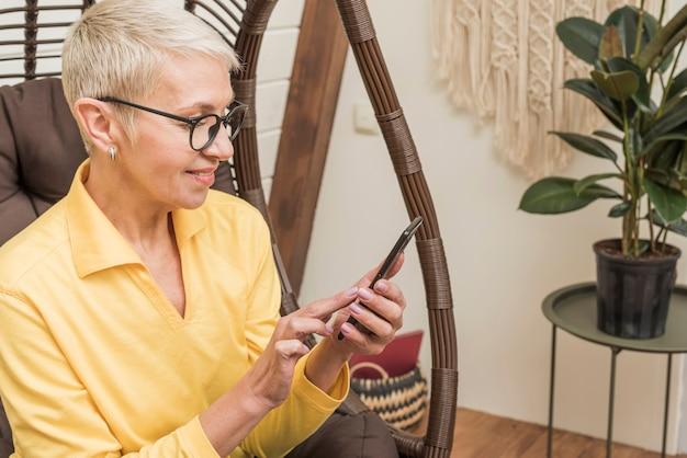 Взгляд со стороны красивая старшая женщина используя ее телефон