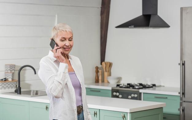Пожилая женщина разговаривает по телефону