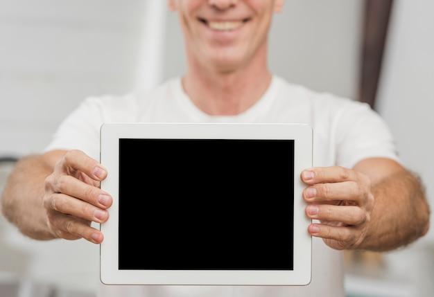 Старший мужчина держит пустой планшет