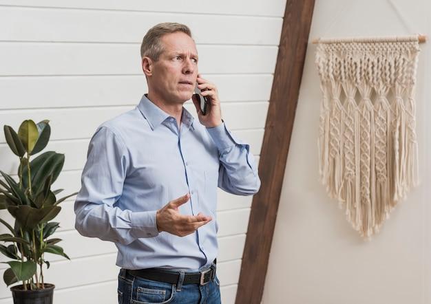 電話で話している年配の男性人