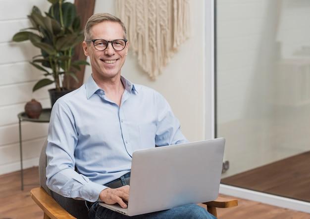 Старший мужчина в очках держит ноутбук