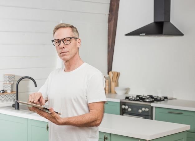 台所で彼のタブレットを保持している現代の年配の男性