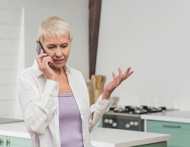 Вид спереди старшая женщина разговаривает по телефону