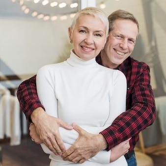 正面の年配の男性が彼の妻を両腕に抱えて