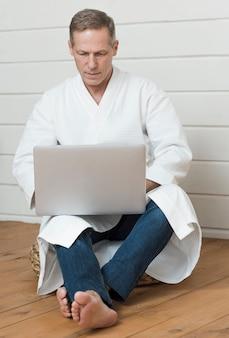 年配の男性が自宅で彼のラップトップを使用して