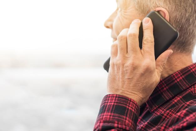 電話のクローズアップで話しているサイドビュー中年の男性