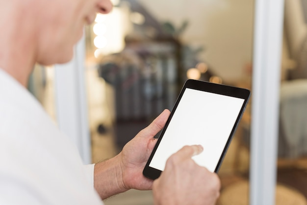 Зрелый человек с помощью планшета в помещении
