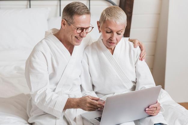 ベッドでノートパソコンを探している正面年配のカップル