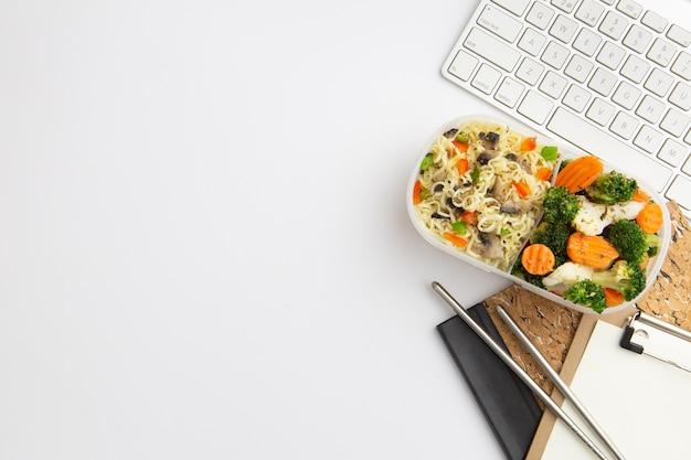 Вид сверху современного рабочего места с едой и копией пространства