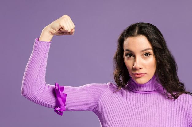 彼女の筋肉の正面を示す女性