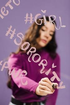 Затуманенное женщина, пишущая «женский клуб» на прозрачном стекле
