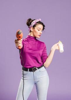 ドリルと哺乳瓶の正面を保持している実用的な女性のミディアムショット