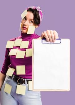 クリップボードを保持している彼女に付箋を持つ女性