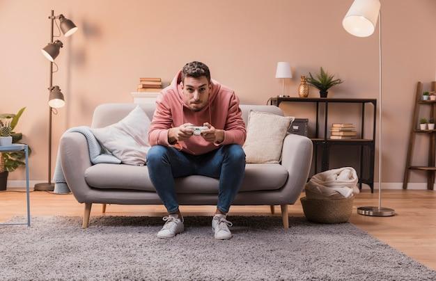 Концентрированный человек на диване играет