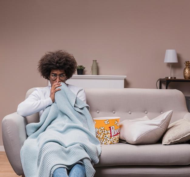 ポップコーンとソファの上の若い男
