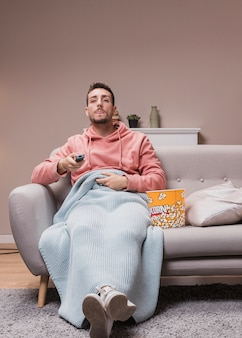 自宅で若い男がテレビを見て