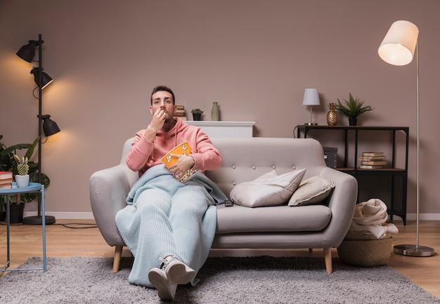 テレビを見ているポップコーンを持つ男性