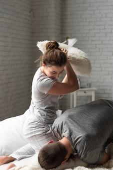 屋内で戦う若い男と女の枕